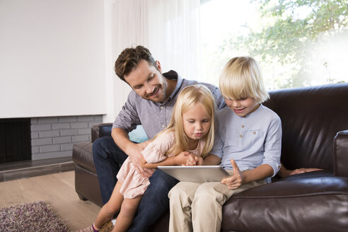 Father and son sitting on couch at home using tablet - MFRF01103
