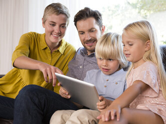 Family sitting on couch at home using tablet - MFRF01106