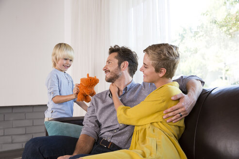 Parents embracing on couch at home and boy playing with cuddly toy - MFRF01109