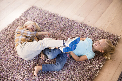 Playful brother and sister lying on carpet at home - MFRF01112