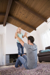 Father playing with daughter on carpet in living room at home - MFRF01115