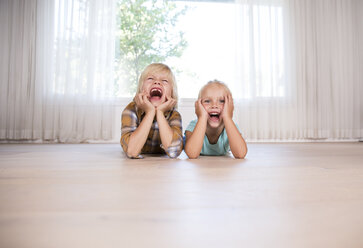 Brother and sister lying on the floor at home grimacing - MFRF01118