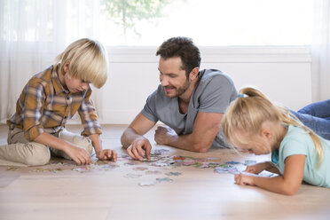 Father with two children lying on the floor at home playing jigsaw puzzle - MFRF01121