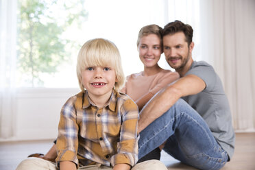 Portrait of smiling boy with parents in background sitting on the floor at home - MFRF01124