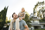 Happy boy on father's shoulders in front of their home - MFRF01127
