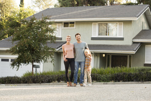 Portrait of smiling parents with boy standing in front of their home - MFRF01133