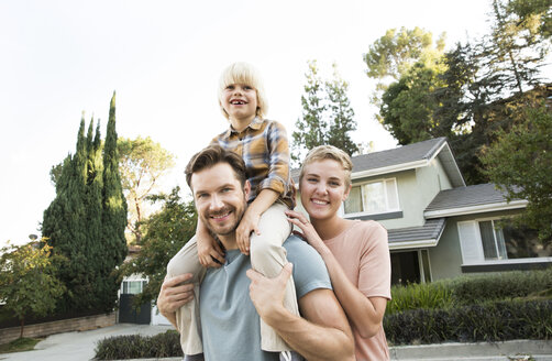 Portrait of smiling parents with son in front of their home - MFRF01136