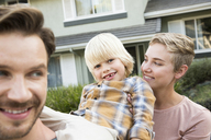 Portrait of happy parents with son in front of their home - MFRF01139