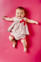 Portrait of happy baby girl lying on pink background - JRFF01487