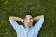 Man relaxing on a meadow, top view - BSZF00137