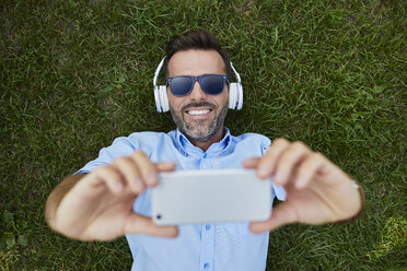 Portrait of laughing man lying on a meadow taking selfie with smartphone, top view - BSZF00140