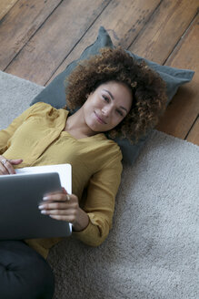 Smiling young woman lying on the floor at home with laptop - HHLMF00063