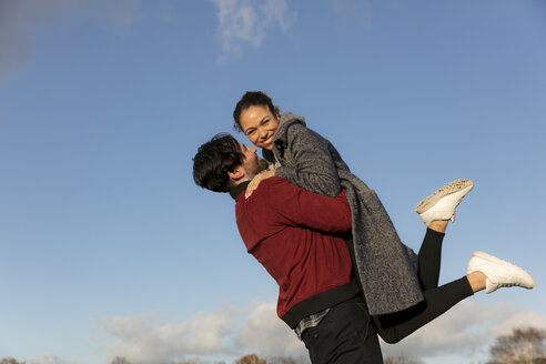 Happy young couple embracing outdoors - HHLMF00075