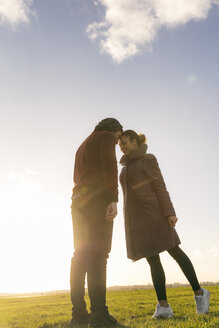 Affectionate young couple standing on a meadow at sunset - HHLMF00078