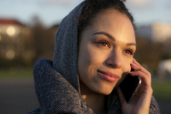 Portrait of smiling young woman on cell phone outdoors - HHLMF00096