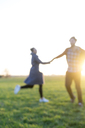 Blurred view of couple on a meadow at sunset - HHLMF00105