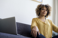 Young woman sitting on couch at home next to laptop - HHLMF00114