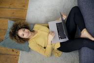 Smiling young woman lying on the floor at home using laptop - HHLMF00120