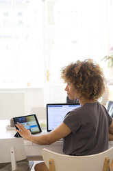 Young woman at home using laptop and tablet - HHLMF00126