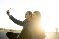 Young couple taking selfie at sunset - HHLMF00147