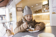 Belgium, portrait of boy eating Belgian waffle with whipped cream in winter outdoors - KMKF00105