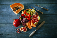 Papaya salad, pomegranate, lettuce, tomato, olives and endive on blue wood - KIJF01820