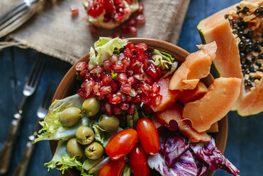 Close-up of papaya salad, pomegranate, lettuce, tomato, olives and endive in bowl - KIJF01823