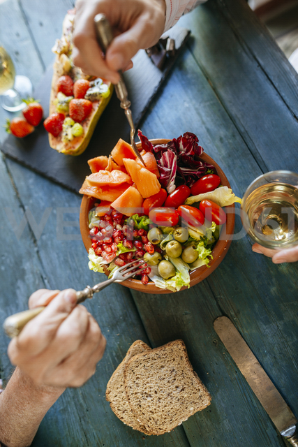 Close-up of woman's hands eating salad of tomato, pomegranate, papaya and olives - KIJF01835