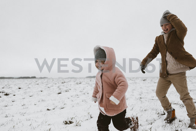 Brother and little sister playing together on snow-covered meadow - KMKF00113