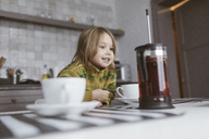 Portrait of smiling little girl in the kitchen - KMKF00119