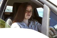 Portrait of young woman with freckles driving car - SRYF00698