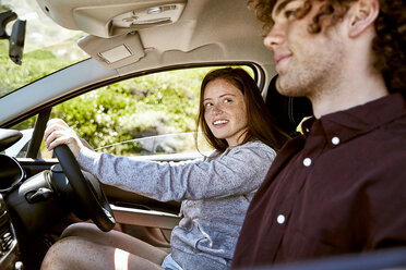 Smiling young woman driving car looking at her boyfriend - SRYF00701