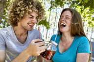 Laughing young couple having a drink in forest - SRYF00713