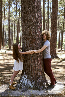 Happy young couple hugging a tree in forest - SRYF00722