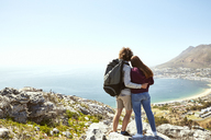 South Africa, Cape Town, young couple on a trip at the coast looking at view - SRYF00728