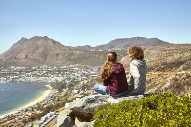 South Africa, Cape Town, young couple sitting at the coast looking at view - SRYF00731