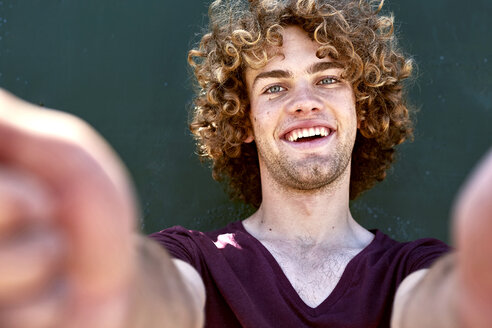 Portrait of laughing young man with curly hair in front of a green wall - SRYF00758