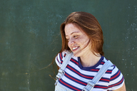 Smiling young woman with freckles in front of green wall - SRYF00764