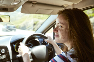Smiling young woman with freckles driving car looking sideways - SRYF00767