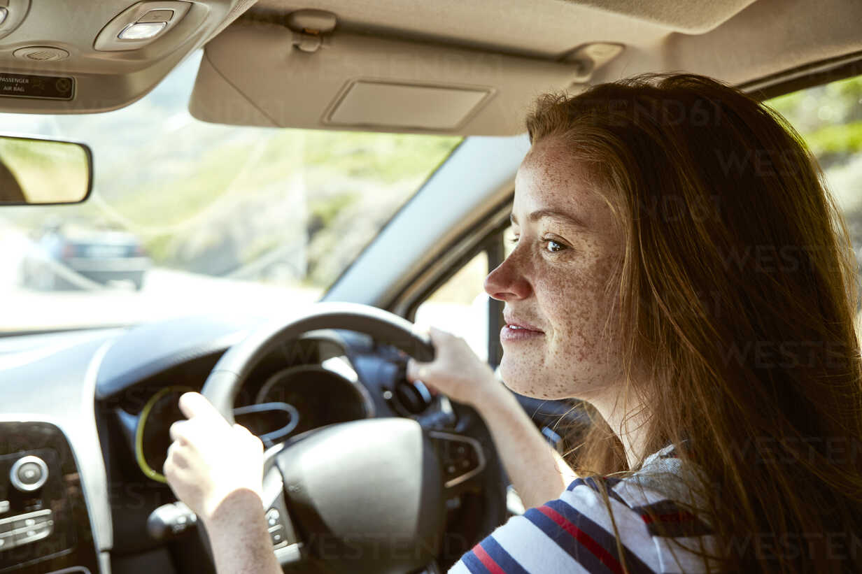 Smiling young woman with freckles driving car looking sideways - SRYF00767 - Martina Ferrari/Westend61