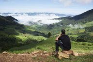 Thailand, Phu Chi Fa, traveler sitting at the top of a hill with view over rice fields - IGGF00340
