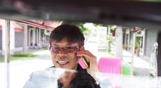 Thailand, Bangkok, tuk tuk driver talking on cell phone - IGGF00347