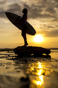 Indonesia, Bali, Silhouette of young woman with surfboard against evening sun - KNTF00950