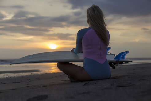 Indonesia, Bali, young woman with surfboard sitting on beach at sunset - KNTF00953