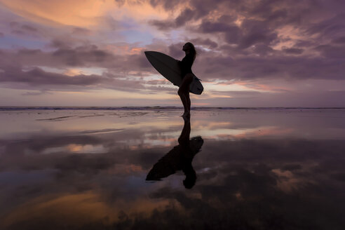 Indonesia, Bali, young woman with surfboard - KNTF00956