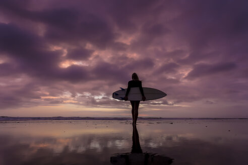 Indonesia, Bali, young woman with surfboard in the evening - KNTF00959
