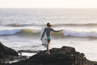 Indonesia, Bali, young woman with surfboard - KNTF00962