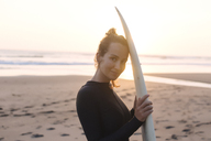 Indonesia, Bali, young woman with surfboard - KNTF00965