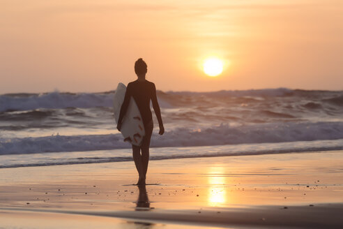 Indonesia, Bali, young woman with surfboard at sunset - KNTF00968