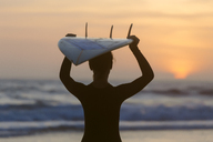 Indonesia, Bali, young woman with surfboard carrying on head at sunset - KNTF00971